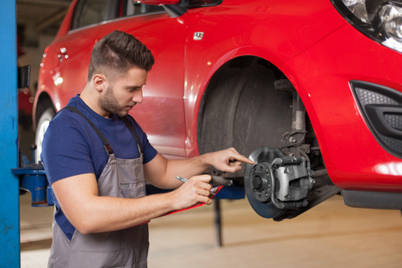 Mechanic holding a clipboard and pointing at car brakes in auto repair shop. Waist up shot in auto repair shop. Stockfoto