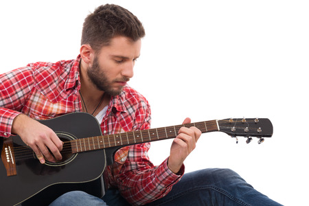 lumberjack shirt: Guitarist in red lumberjack shirt sitting and play the black acoustic guitar. Studio portrait isolated on white. Stock Photo