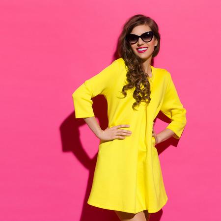 three quarter length: Smiling beautiful girl in yellow mini dress posing against pink background. Three quarter length studio shot. Stock Photo