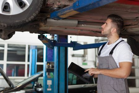 chassis: Focused mechanic standing under car holding a digital tablet and checking a chassis Stock Photo