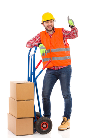 Smiling man in yellow hardhat and orange reflective vest lean on a delivery cart and showing thumb up. Full length studio shot isolated on white.