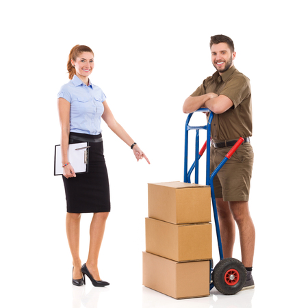 messengers: Office female worker pointing at messengers delivery cart with a stack of boxes. Full length studio shot isolated on white.