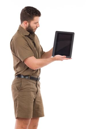 clothes organizer: Man in khaki uniform presenting a shockproof  digital tablet. Three quarter length studio shot isolated on white. Stock Photo
