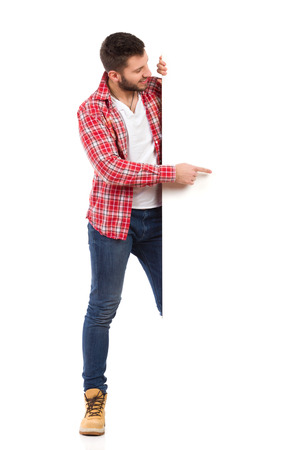 lumberjack shirt: Handsome young man in jeans and lumberjack shirt standing behind white banner and pointing. Full length studio shot isolated on white.