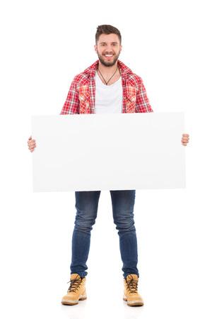 lumberjack shirt: Smiling man in red lumberjack shirt holding white banner. Full length studio shot isolated on white.