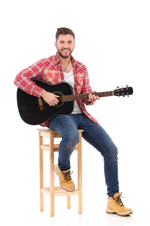 guy playing guitar: Man in red lumberjack shirt sitting on a chair and holding acoustic guitar. Studio portrait isolated on white.