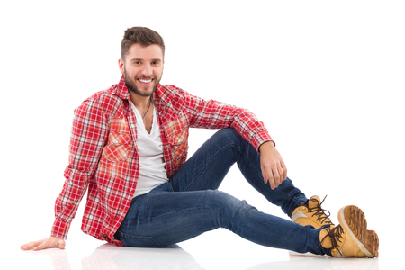 lumberjack shirt: Relaxed young man in lumberjack shirt sitting on a floor. Full length studio shot isolated on white.