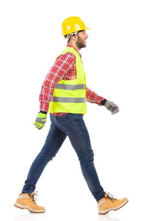 黄色いヘルメットとライム反射ベスト建設労働者を歩きます。完全な長さのスタジオ撮影に分離白。
