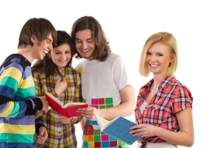 waist shot: Smiling female student holding a book and standing against a group of friends. Waist up studio shot isolated on white.