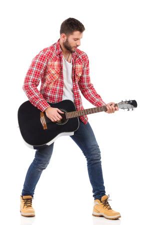 hombre rojo: Guitarrista en la camisa de le�ador rojo que se coloca con la guitarra ac�stica negro. Estudio de longitud completa aislado disparo en blanco.
