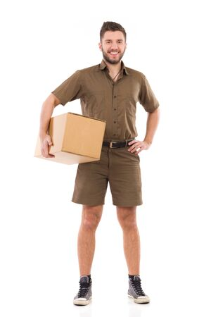 Smiling courier standing and holding carton box under the arm. Full length studio shot isolated on white. Banco de Imagens