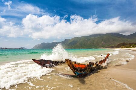 con dao: Old destroyed wooden boat on a sandy beach, hit by a sea wave on a Con dao Island in Vietnam Stock Photo