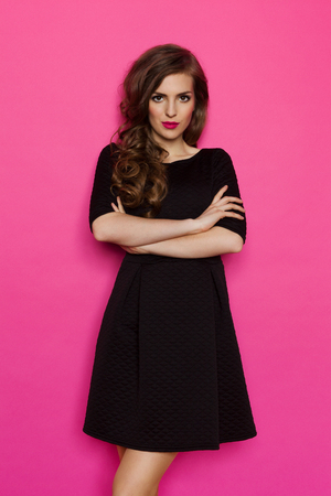 Elegance woman in black dress standing with arms crossed. Three quarter length studio shot on pink background.