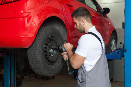 waist shot: Car mechanic changing the wheel with an impact wrench. Waist up shot in auto reapir shop.