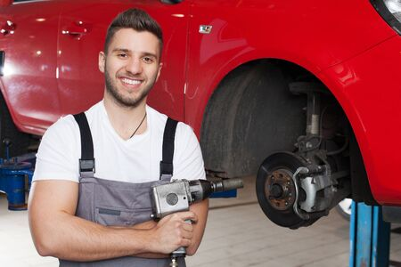 impact wrench: Smiling man in workwear posing with an impact wrench against red car in workshop