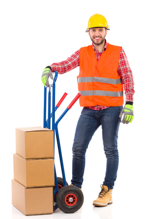 leaning on the truck: Smiling man in yellow hardhat and orange reflective vest posing with a delivery cart and looking at camera. Full length studio shot isolated on white.