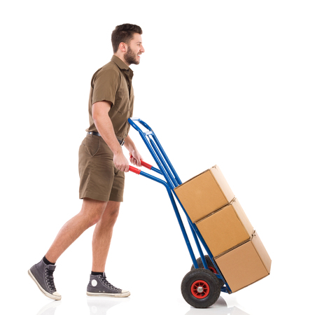push cart: Happy messenger walking with a push cart. Full length studio shot isolated on white.