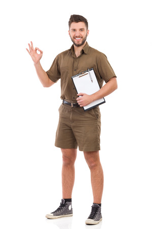courier: Happy courier holding a clipboard under the arm and showing ok sign. Full length studio shot isolated on white.