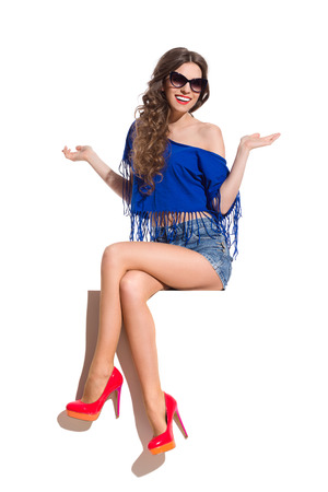 legs crossed at knee: Smiling young woman in sunglasses, blue top, jeans shorts and red high heels sitting at the white banner with legs crossed at knee and arms outstretched. Full length studio shot isolated on white. Stock Photo