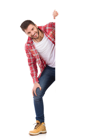 lumberjack shirt: Handsome young man in jeans and lumberjack shirt standing behind white banner and smiling. Full length studio shot isolated on white.