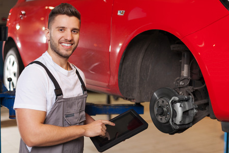 Smiling man in workshop standing close to car brake disc and pointing at a digital tablet. Stockfoto