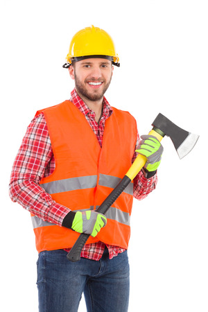 three quarter length: Smiling lumberjack in yellow helmet and orange waistcoat posing with an axe. Three quarter length studio shot isolated on white. Stock Photo