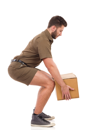 Man in khaki uniform picking up a carton box, side view. Full length studio shot isolated on white.