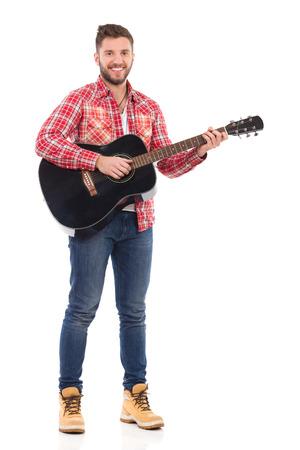 lumberjack shirt: Guitarist in red lumberjack shirt posing with the black acoustic guitar. Full length studio shot isolated on white. Stock Photo