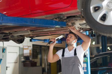Focused mechanic standing under car holding lamp and checking a chassis