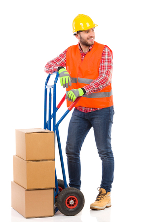 leaning on the truck: Smiling man in yellow hardhat and orange reflective vest posing with a delivery cart and looking away. Full length studio shot isolated on white.