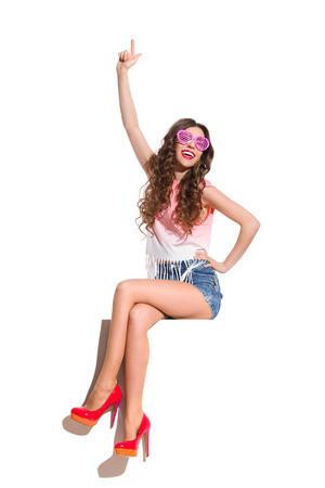legs crossed at knee: Shouting sexy woman in pink heart shaped sunglasses, pink top, jeans shorts and red high heels sitting at the white banner and pointing up. Full length studio shot isolated on white.