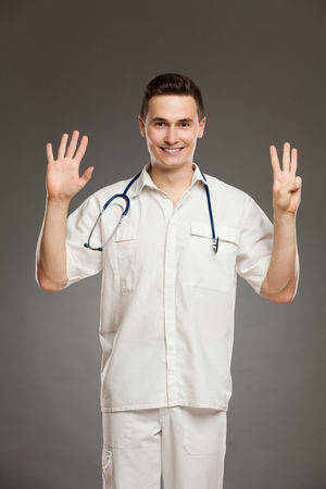 hand sign: Portrait of a smiling doctor showing number eight  with his fingers. Three quarter length studio shot on gray background.