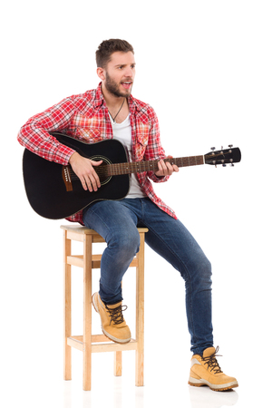 lumberjack shirt: Singing guitarist in red lumberjack shirt sitting on a chair play the black acoustic guitar. Studio portrait isolated on white. Stock Photo