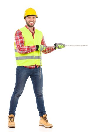 reflective vest: Smiling manual worker in yellow helmet and lime reflective vest pulling a chain. Full length studio shot isolated on white. Stock Photo