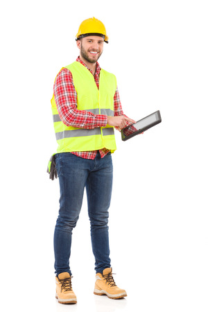 clothes organizer: Manual worker in yellow helmet and lime vest holding a shockproof digital tablet. Full length studio shot isolated on white. Stock Photo