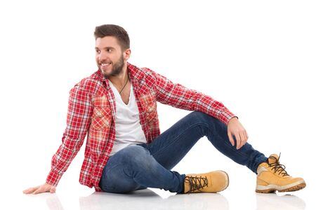 lumberjack shirt: Relaxed young man in lumberjack shirt sitting on floor and and looking away. Full length studio shot isolated on white. Stock Photo