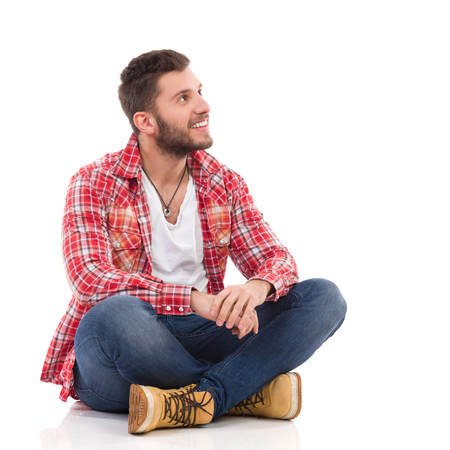 Handsome young man in jeans and lumberjack shirt sitting on floor with legs crossed and looking up. Full length studio shot isolated on white.