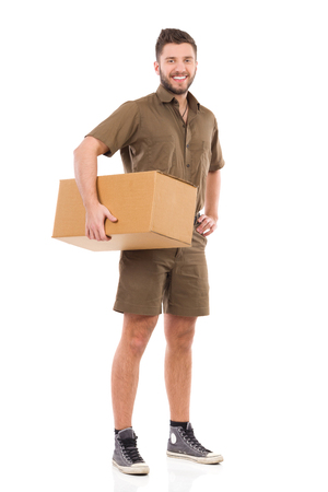 cardboard only: Smiling messenger standing and holding carton box under the arm. Full length studio shot isolated on white.