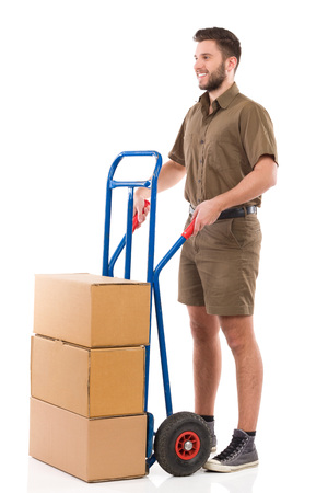 push cart: Happy delivery man standing with a push cart. Full length studio shot isolated on white.