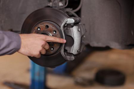 Mechaniker Hand zeigt auf Bremsbeläge