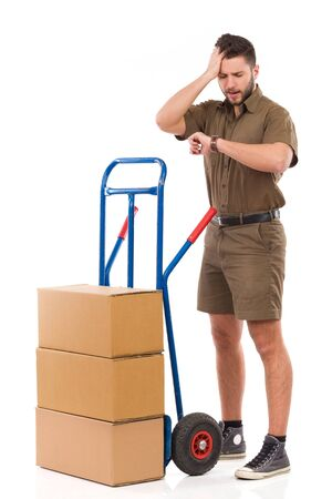 push cart: Delivery man standing close to a push cart, checking time at wristwatch and holding hand on head. Full length studio shot isolated on white. Stock Photo