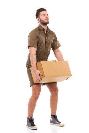 ダン ボール箱をカーキ色制服拾いに配達人。完全な長さのスタジオ撮影に分離白。