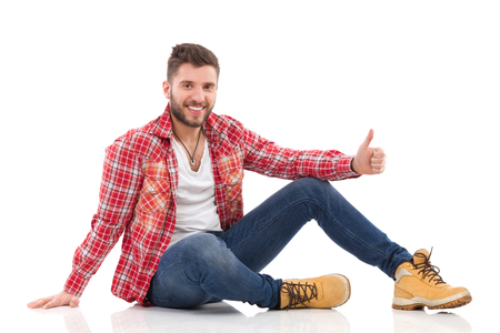 Relaxed young man in lumberjack shirt sitting on a floor and showing thumb up. Full length studio shot isolated on white.