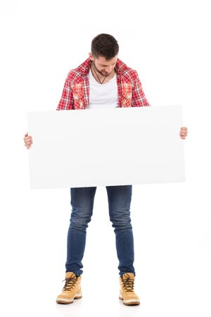 lumberjack shirt: Man in red lumberjack shirt holding white banner and reading. Full length studio shot isolated on white. Stock Photo