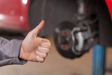 Mans hand showing thumb up against brake disc