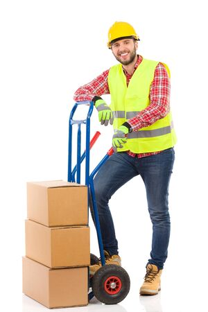 leaning on the truck: Relaxed manual worker lean on the push cart. Full length studio shot isolated on white.