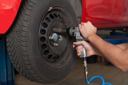 impact wrench: Close up of mans hands changing wheel. Hands holding a impact wrench.