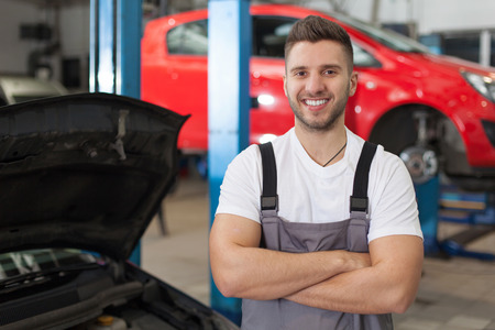 waist shot: Smiling man in workshop posing with arms crossed. Waist up shot in auto repair shop.