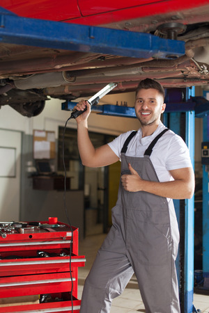 chassis: Smiling man in workwear checking car chassis and showing thumb up.