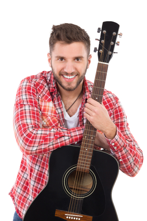 waist shot: Guitarist in red lumberjack shirt posing with a black acoustic guitar. Waist up studio shot isolated on white.